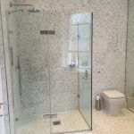 Modern bathroom with glass shower stall and grey tiles